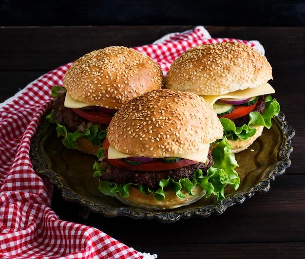 Três hambúrgueres com uma costeleta de carne, legumes e queijo
