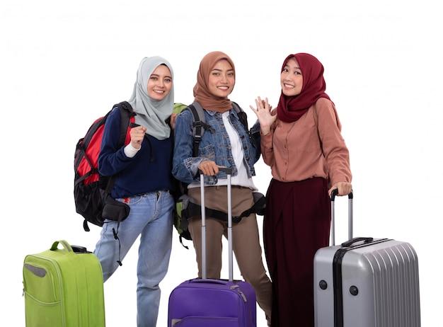 Três hijab mulher em pé segurando a mala e carregando o saco