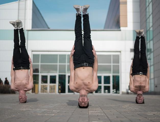 Três hip-hop sem camisa em pé sobre suas cabeças