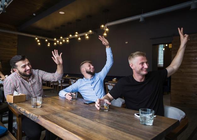 Três homem sentado no restaurante cumprimentando seus amigos