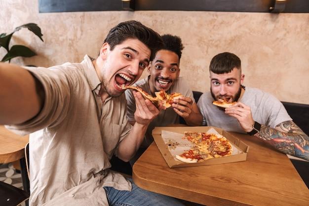 Três homens alegres comendo pizza na mesa do café dentro de casa, tirando uma selfie