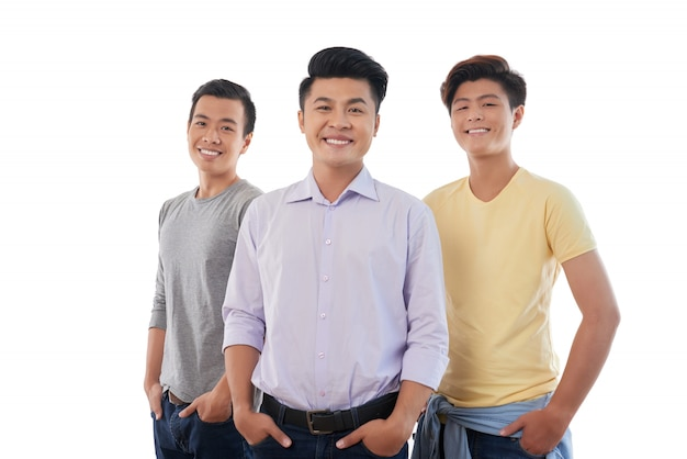 Três homens asiáticos em pé com as mãos nos bolsos e sorrindo para a câmera