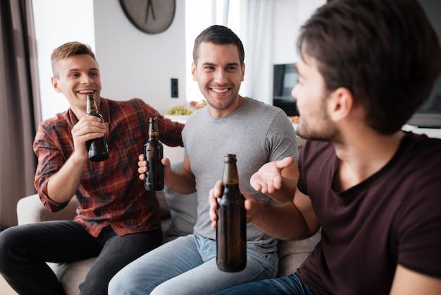 Três homens bebem cerveja de garrafas escuras.