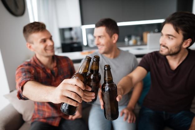 Três homens bebem cerveja. os caras seguram garrafas escuras.