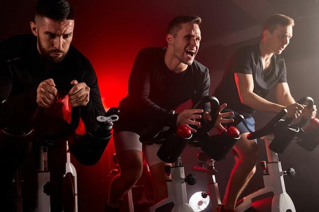 Três homens de fitness em bicicleta de ginástica, treinando em uma bicicleta ergométrica em uma academia no espaço escuro, concentrados em exercícios