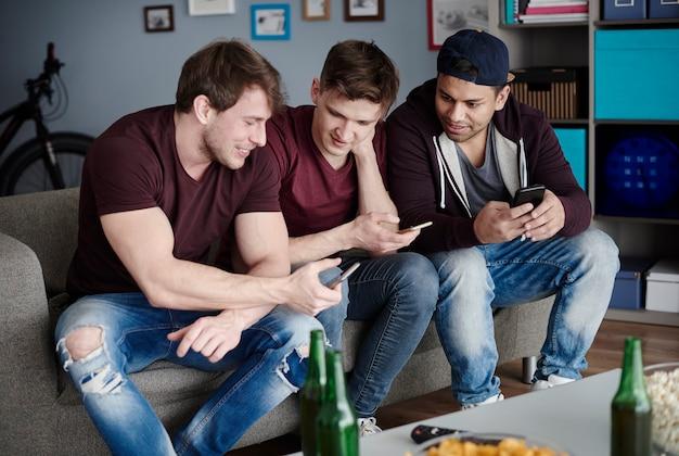 Três homens em roupas esportivas usando smartphones