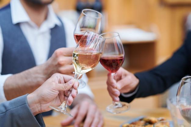 Três humanos tilintando em taças de vários tipos de vinho enquanto fazem um brinde comemorativo
