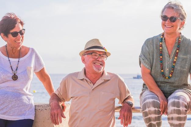 Três idosos e adultos sentados na praia com o mar ao fundo se divertindo e rindo juntos