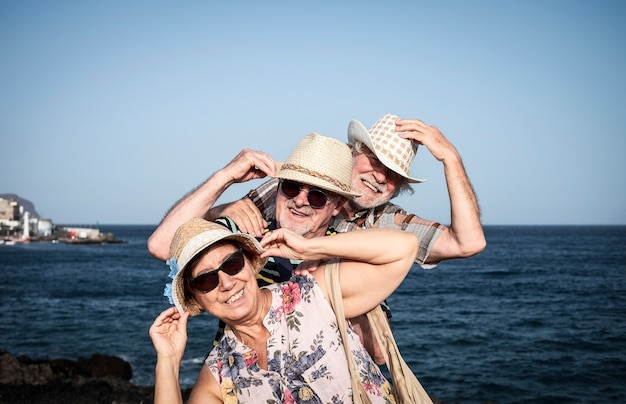 Três idosos sorridentes e felizes desfrutam de uma excursão marítima nas férias de verão - conceito de idosos brincalhões ativos durante a aposentadoria - horizonte sobre a água
