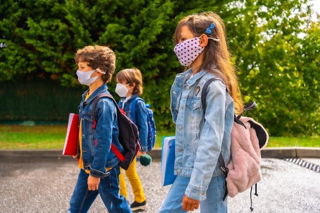 Três irmãos com máscaras prontos para voltar às aulas. nova normalidade, distância social, pandemia de coronavírus, covid-19. deixando o lar