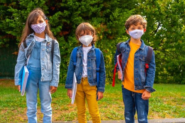 Três irmãos com máscaras prontos para voltar às aulas. nova normalidade, distância social, pandemia de coronavírus, covid-19. esperando para ir para a escola com plantas verdes ao fundo