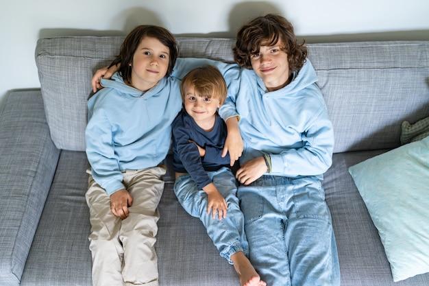 Três irmãos de diferentes idades estão sentados em um sofá em casa. os meninos mais velhos abraçam os mais novos. boas relações entre irmãos.