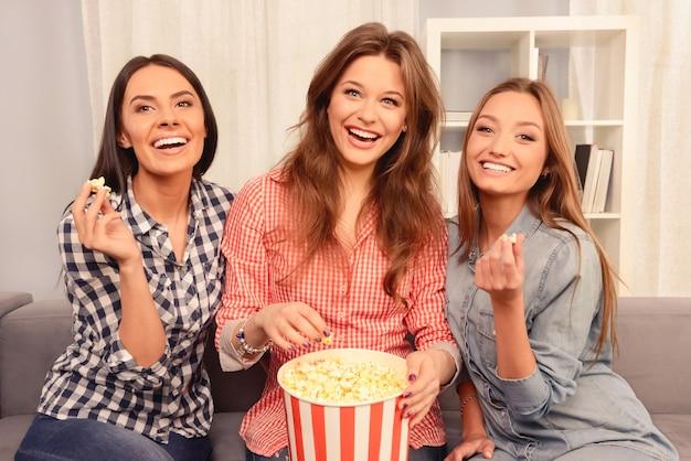 Três irmãs assistindo filme interessante e comendo pipoca
