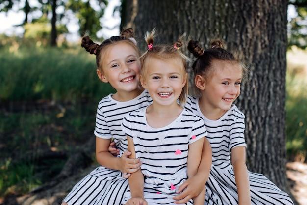 Três irmãs felizes em vestidos sorriem e se abraçam no parque