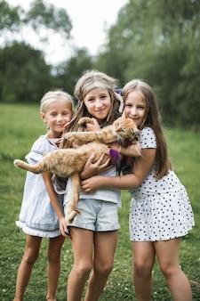 Três irmãs meninas brincando e acariciando gato vermelho