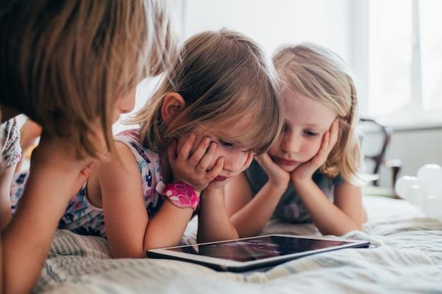 Três irmãzinhas indoor em casa usando tablet deitado na cama