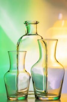 Três itens - vasos transparentes e uma garrafa. ainda vida abstrata, em uma parede colorida de verde-amarelo.