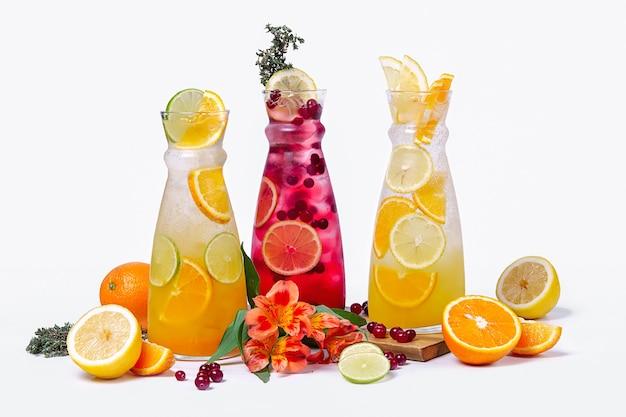 Três jarras com frutas de verão e coquetéis de frutas vermelhas no fundo branco
