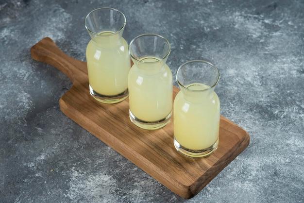 Três jarras de vidro de limonada fresca em uma placa de madeira