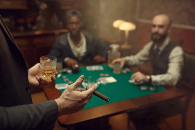 Três jogadores de pôquer sentados à mesa no cassino