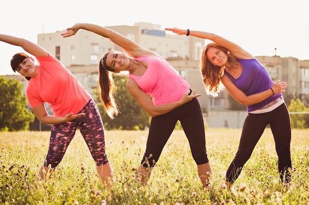 Três jovem exercitando juntos em um parque