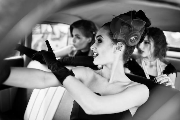 Três jovem num assento de vestido estilo retro velho carro antigo clássico e se divertindo emoções