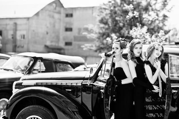 Três jovem num vestido de estilo retro, perto de carros antigos clássicos antigos.