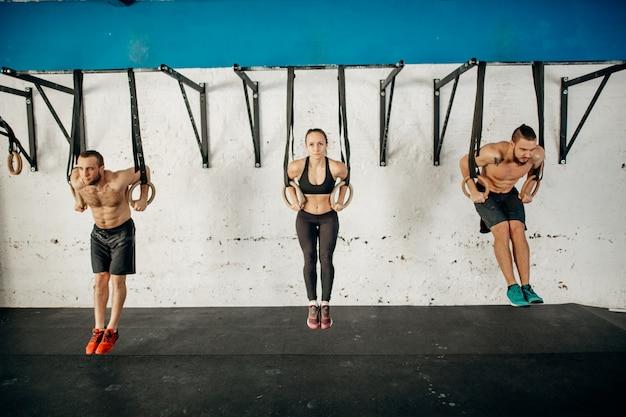 Três jovens adultos masculinos e femininos fazendo pull ups em anéis