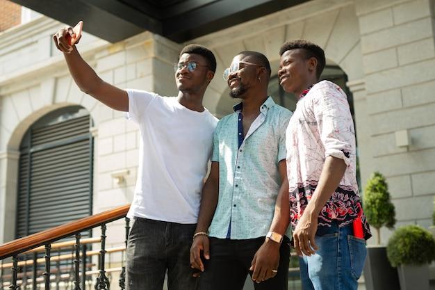 Três jovens africanos são fotografados ao telefone