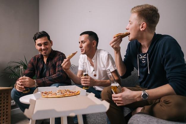 Três jovens alegres comendo pizza tirando-a da mesa