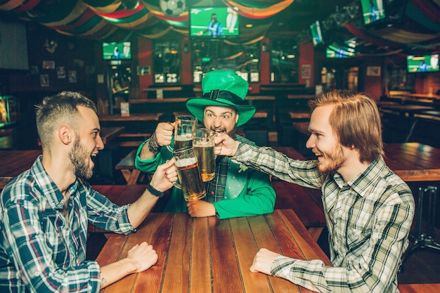 Três jovens alegres sentam-se à mesa no pub e juntam canecas de cerveja. cara no meio usa roupa de são patrício. eles gritam e sorriem. as pessoas gostam de companhia.