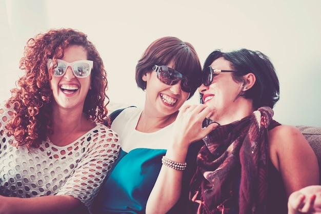 Três jovens amigas loucas se divertindo muito em casa no sofá