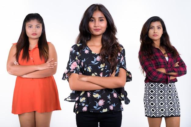 Três jovens amigas persas de braços cruzados