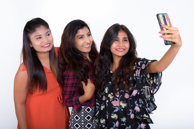 Três jovens amigas persas felizes sorrindo enquanto tiravam uma selfie