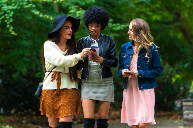 Três jovens amigos andando por um parque e olhando para um folheto, uma loira, uma morena e uma garota latina com cabelo afro