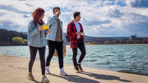 Três jovens amigos caminhando à beira do lago, bebendo e comendo em um parque