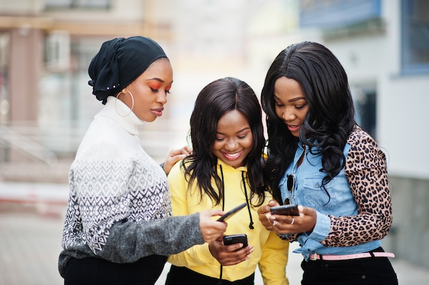 Três jovens amigos da mulher afro-americana com telefones celulares.