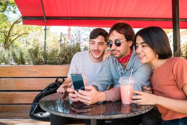 Três jovens amigos tomando uma selfie com telefone.