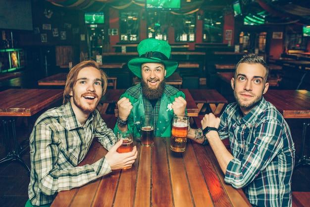 Três jovens animado torcendo na mesa no pub. eles olham para frente e sorriem. o cara do meio usa o traje do st. patrick.