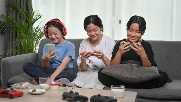 Três jovens asiáticas usando telefone inteligente e sentados juntos no sofá em casa.