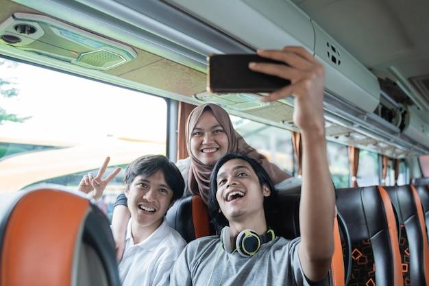 Três jovens asiáticos sorriem e posam para a câmera do celular enquanto tiram uma selfie juntos no ônibus