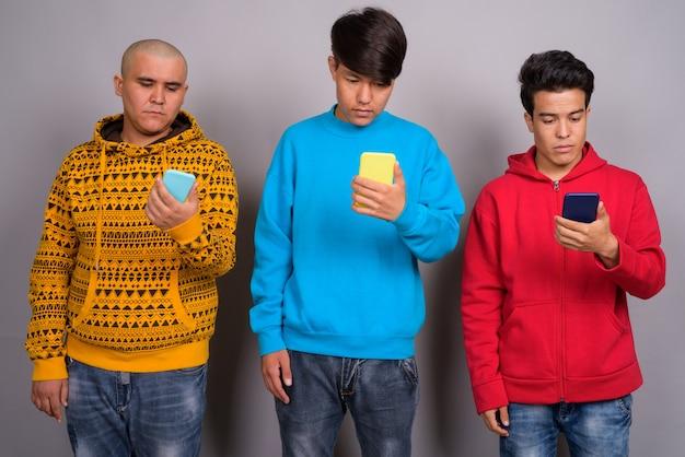 Três jovens asiáticos vestindo roupas quentes contra parede cinza