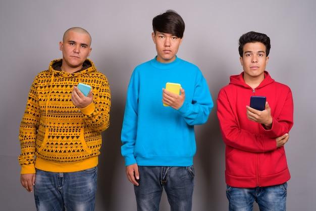Três jovens asiáticos vestindo roupas quentes contra um fundo cinza