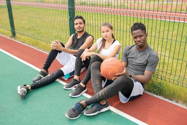 Três jovens atletas em roupas esportivas sentados em uma quadra de basquete ao ar livre perto da rede e descansando após o jogo