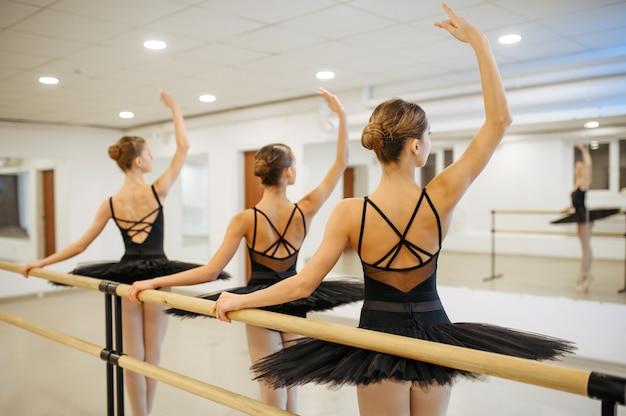 Três jovens bailarinas, alunos ensaiando na barra em sala de aula