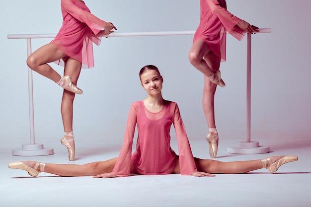 Três jovens bailarinas em um vestido rosa estendendo-se no balcão sobre fundo bege