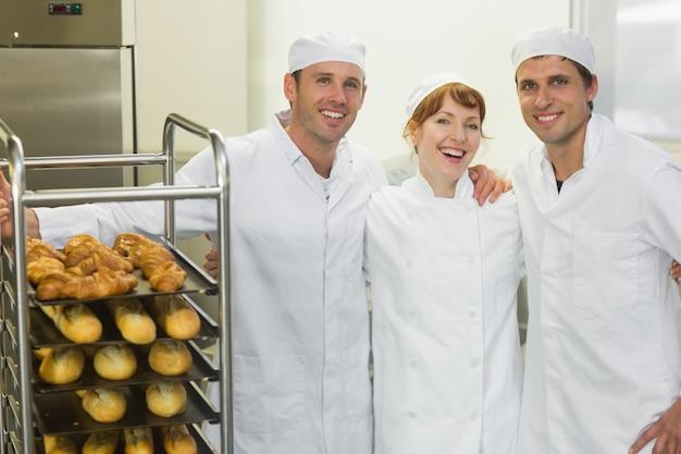Três jovens bolos posando juntos em uma padaria