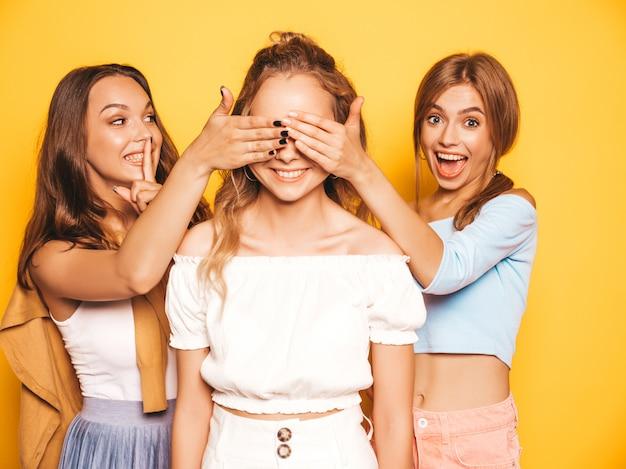 Três jovens bonitas garotas hipster sorridentes em roupas da moda no verão. mulheres despreocupadas sexy posando perto da parede amarela. modelos surpreendendo seu amigo. eles cobrem os olhos dela e abraçando por trás