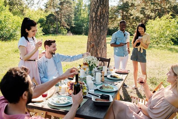 Três jovens casais felizes em trajes casuais curtindo o dia de sol enquanto um deles rolava em seus smartphones perto de um pinheiro na grama verde