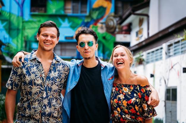 Três jovens de diferentes etnias se abraçando pelas costas e sorrindo no meio de uma rua com fachadas coloridas decoradas com arte de rua